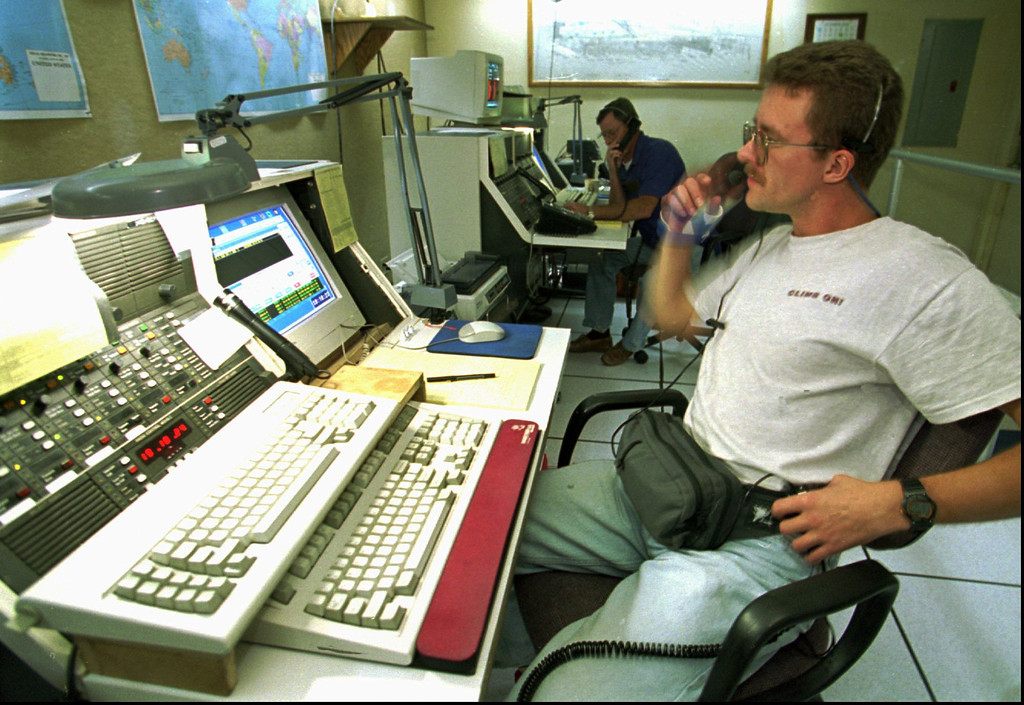 . U.S. Border Patrol agent Glenn Merrill, foreground, radios field agents the positions of possible illegal immigrants Tuesday Oct. 24, 1995 in San Diego. Merrill monitors part of a network of over 600 seismic sensors that detect movement near the U.S./Mexico border. (AP Photo/Denis Poroy)