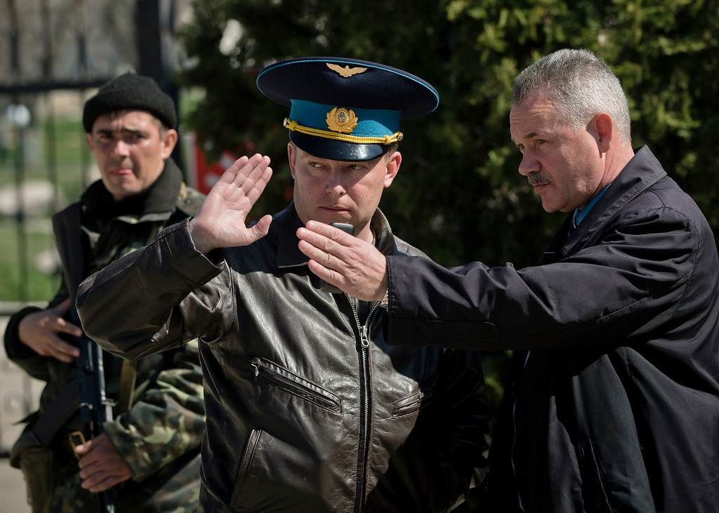. Belbek air base commander Col. Yuliy Mamchur, center, reacts to a request to leave the base by a leader of Crimea\'s self defense units, right, who declined to be identified, near the main gate of the base, outside Sevastopol, Crimea, Friday, March 21, 2014.  Mamchur said he was asked by the Russian military to turn over the base but is unwilling to do so until he receives orders from the Ukrainian defense ministry. (AP Photo/Vadim Ghirda)