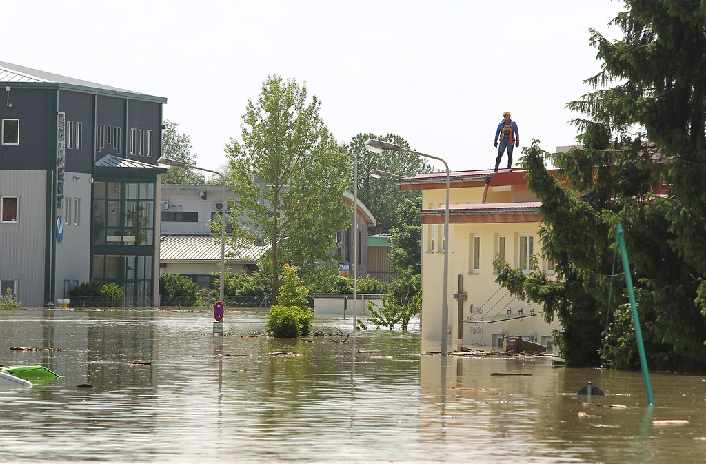 . A helper stands on the roof of a flooded house in Deggendorf, southern Germany, on June 5, 2013.      AFP PHOTO / KARL-JOSEF HILDENBRAND /AFP/Getty Images