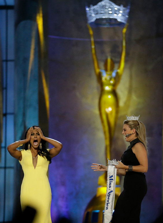 . Miss New York Nina Davuluri, left, reacts after winning the Miss America 2014 pageant as Miss America 2013 Mallory Hagan approaches her, Sunday, Sept. 15, 2013, in Atlantic City, N.J. (AP Photo/Julio Cortez)