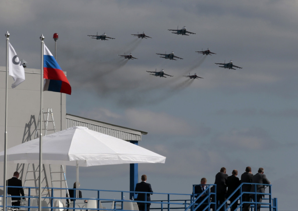 ". Visitors watch Russian pilot group the ""Russian Knights\"" along with the \""Strizhi\"" group performing at the opening of the MAKS Air Show in Zhukovsky outside Moscow on Tuesday, Aug. 27, 2013. (AP Photo/Ivan Sekretarev)"