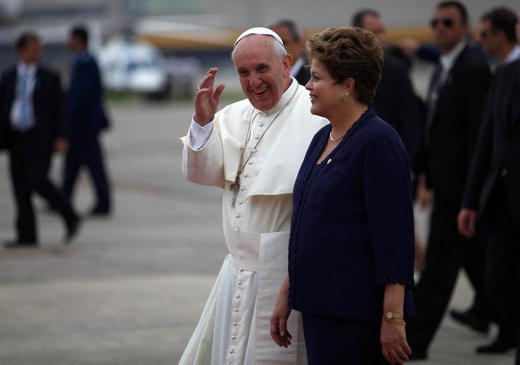 . Pope Francis waves as he is accompanied by Brazil\'s President Dilma Rousseff upon his arrival at the international airport in Rio de Janeiro, Brazil, Monday, July 22, 2013, in his first trip as pontiff to Latin America.  (AP Photo/Jorge Saenz)