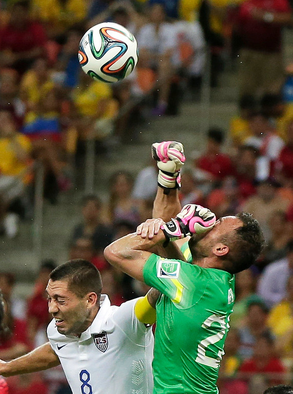. United States\' Clint Dempsey, left, challenges Portugal\'s goalkeeper Beto as Beto punches the ball during the group G World Cup soccer match between the United States and Portugal at the Arena da Amazonia in Manaus, Brazil, Sunday, June 22, 2014. (AP Photo/Marcio Jose Sanchez)