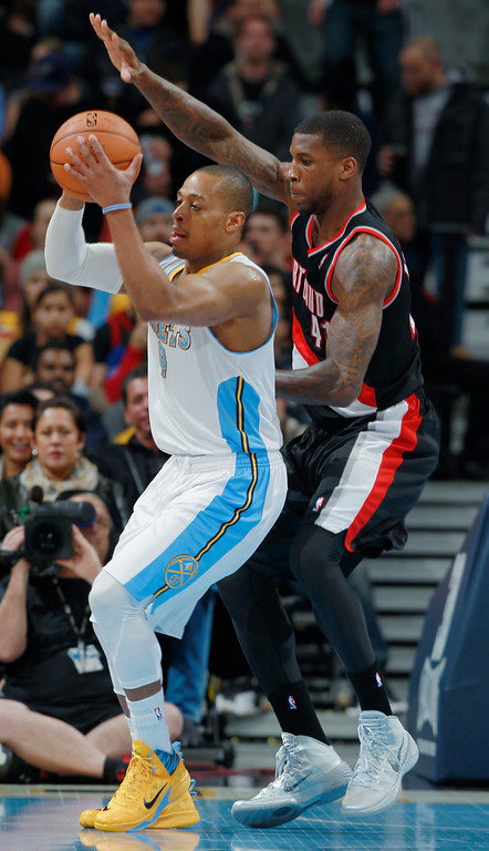 . Denver Nuggets guard Randy Foye, left, pulls in a loose ball as Portland Trail Blazers forward Thomas Robinson covers in the first quarter of an NBA basketball game in Denver, Tuesday, Feb. 25, 2014. (AP Photo/David Zalubowski)