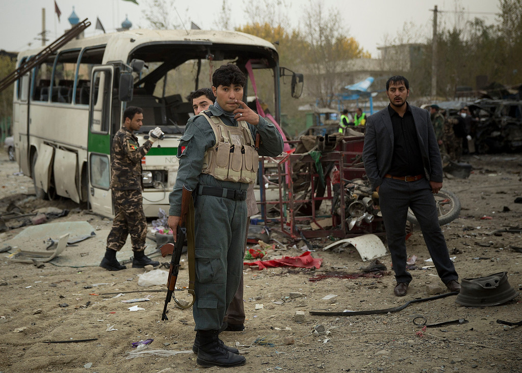 . Afghan policemen arrive to an area after a suicide vehicle bomb tore through the area on the outskirts of Kabul, Saturday, Nov. 16, 2013. (AP Photo/Anja Niedringhaus)
