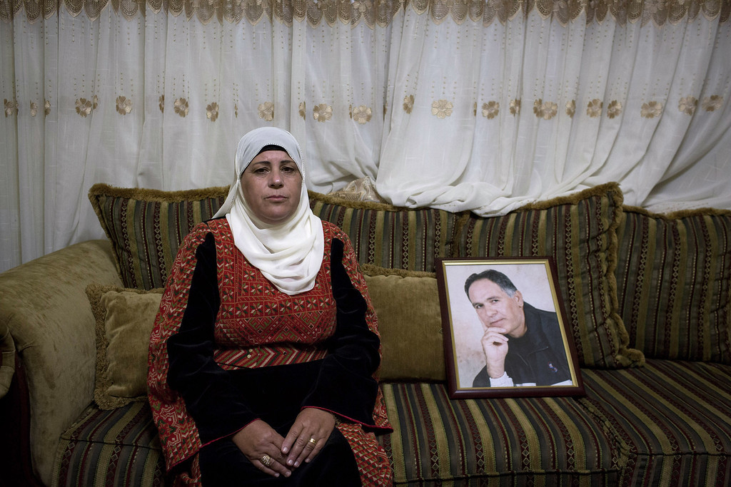 . Samia, the wife of Palestinian prisoner Mohamed Ibrahim, jailed in Israeli prisons since 1985, sits near his photo as she waits for his release as part of a decision to release 26 Palestinian prisoners from Israeli jails, on October 29, 2013 in Safa, West Bank. The 26 Palestinian prisoners are to be freed later tonight as part of the terms of renewed U.S.-brokered peace talks. (Photo by Oren Ziv/Getty Images)