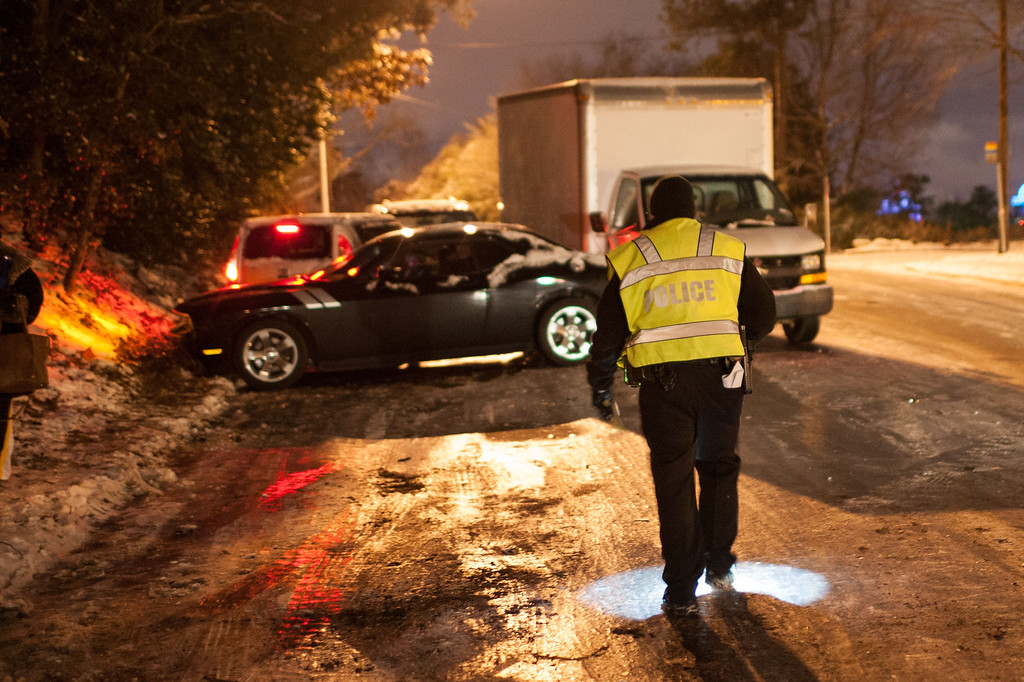 . Officer Delaney walks towards a five-car pileup on Johnson Ferry Road, early Wednesday, Jan. 29, 2014, in Sandy Springs, Ga. Around Atlanta, nearly all public entities and most businesses were shut down early Wednesday, and officials encouraged would-be motorists not to drive. (AP Photo/Branden Camp)