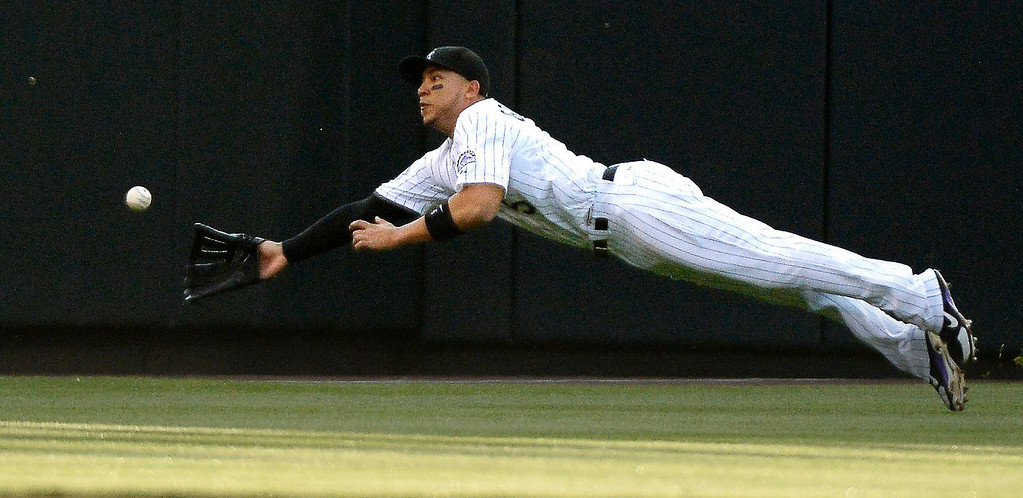 . Carlos Gonzalez (5) of the Colorado Rockies lays out trying to catch a fly ball hit by Gregor Blanco (7) of the San Francisco Giants during the third inning May 16, 2013 at Coors Field. Blanco ended with a double on the play.  (Photo By John Leyba/The Denver Post)
