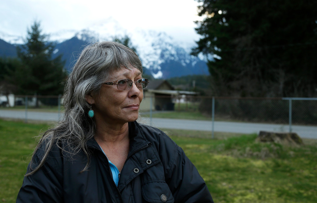 . Robin Youngblood poses for a photo Thursday, March 27, 2014, with Whitehorse Mountain behind her in Darrington, Wash. Youngblood survived the massive mudslide that hit the nearby community of Oso, Wash. last Saturday, and was rescued by a helicopter as she floated on a piece of a roof. (AP Photo/Ted S. Warren)