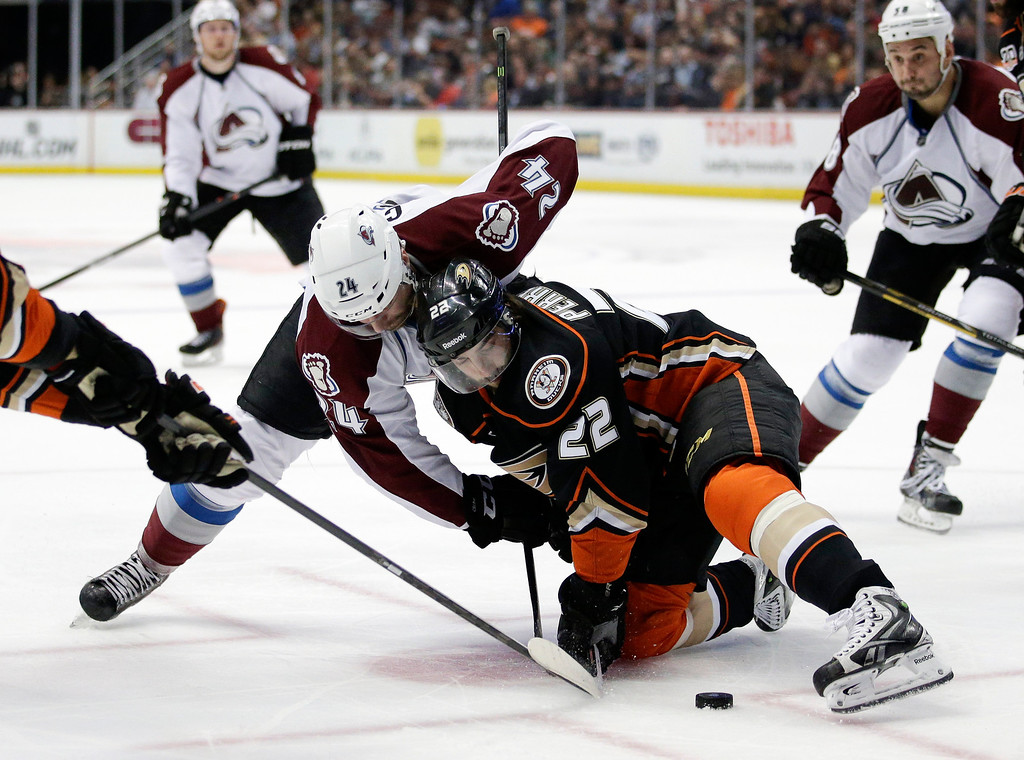 . Colorado Avalanche\'s Marc-Andre Cliche, left, and Anaheim Ducks\' Mathieu Perreault fight for the puck during the first period of an NHL hockey game on Sunday, April 13, 2014, in Anaheim, Calif. (AP Photo/Jae C. Hong)