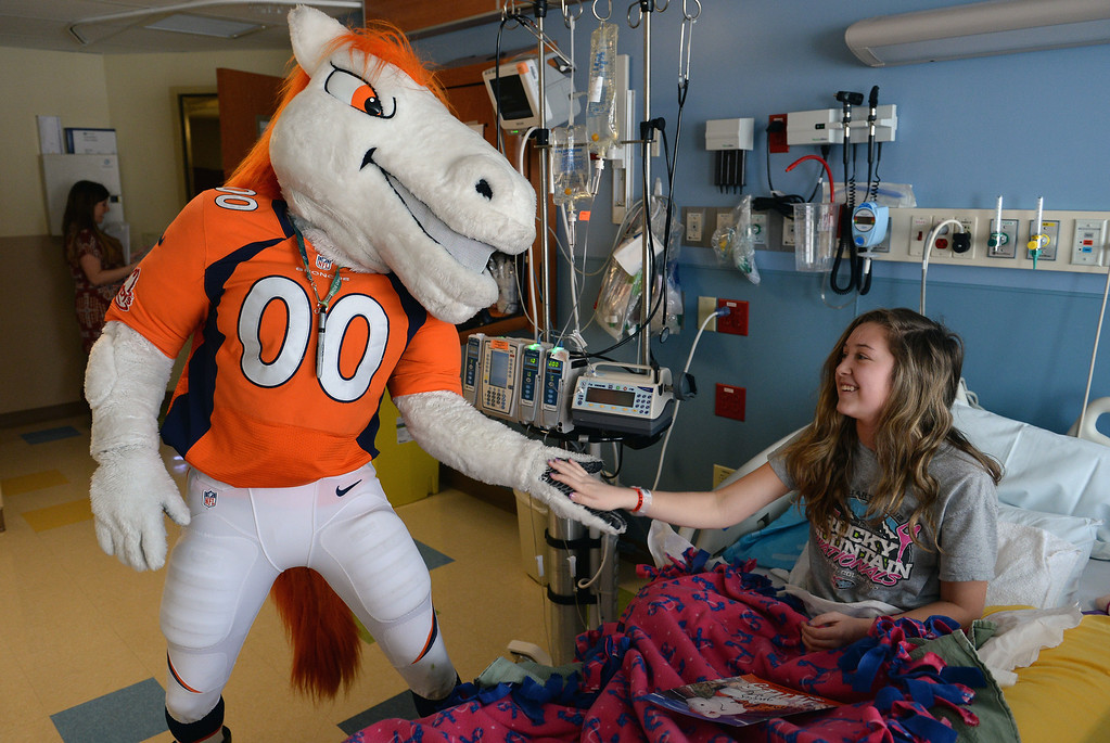. Madeline Conley, 15, gets a low five from Miles, the Broncos Mascot, as he made a surprise visit to her in her room in the Pediatric Intensive Care Unit at the  Rocky Mountain Hospital for Children in Denver, Co on January 14, 2014. Conley was diagnosed with leukemia just 3 days ago.   (Photo By Helen H. Richardson/ The Denver Post)
