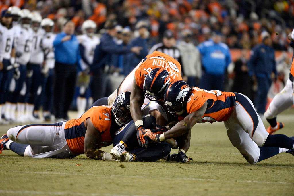 . DENVER, CO - DECEMBER 12: San Diego Chargers running back Danny Woodhead (39) gets tackled by Denver Broncos defensive end Robert Ayers (91), defensive end Malik Jackson (97) and Denver Broncos outside linebacker Danny Trevathan (59) during the third quarter. The Denver Broncos vs. the San Diego Chargers at Sports Authority Field at Mile High in Denver on December 12, 2013. (Photo by John Leyba/The Denver Post)