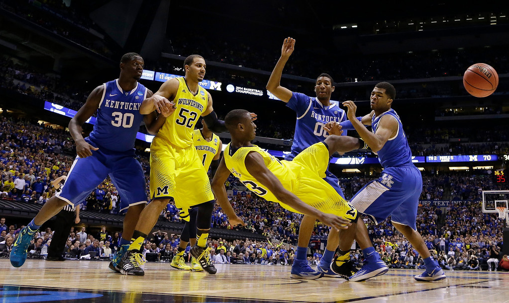 . Michigan\'s Caris LeVert falls as he passes the ball during the second half of an NCAA Midwest Regional final college basketball tournament game against Kentucky Sunday, March 30, 2014, in Indianapolis. (AP Photo/Michael Conroy)