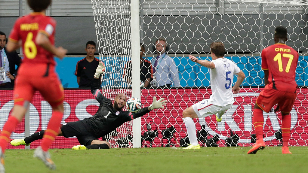 . United States\' goalkeeper Tim Howard (1) dives to make a save as Matt Besler (5) watches with Belgium\'s Divock Origi (17) during the World Cup round of 16 soccer match between Belgium and the USA at the Arena Fonte Nova in Salvador, Brazil, Tuesday, July 1, 2014. At left is Belgium\'s Axel Witsel. (AP Photo/Marcio Jose Sanchez)