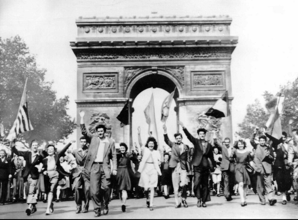 . Parisians march through the Arc de Triomphe jubilantly waving flags of the Allied Nations as they celebrate the end of World War II on May 8, 1945.  German military leaders signed an unconditional surrender in Reims, France, on May 7. (AP Photo)