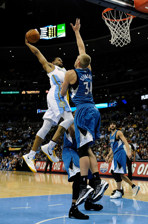 . Denver Nuggets guard Andre Iguodala goes up for a dunk over Minnesota Timberwolves center Greg Stiemsma in the second half of an NBA basketball game on Saturday, March 9, 2013, in Denver.  (AP Photo/Chris Schneider)