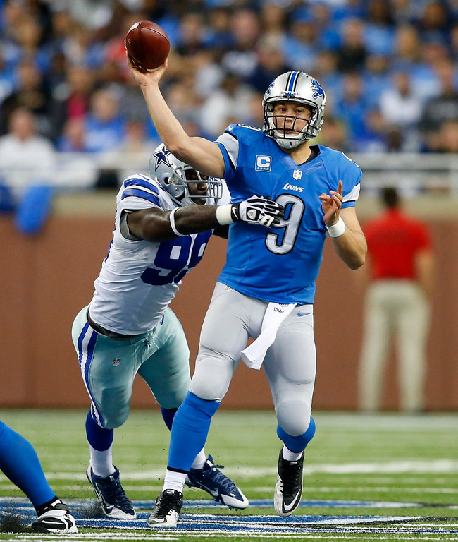 . Detroit Lions quarterback Matthew Stafford (9) throws under pressure from Dallas Cowboys defensive end George Selvie (99) in the second quarter of an NFL football game in Detroit, Sunday, Oct. 27, 2013. (AP Photo/Rick Osentoski)