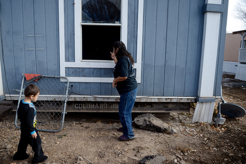 . MILLIKEN, CO - DECEMBER 18: Martha Gutierrez, manager of the Evergreen Mobile Home Park, looks into a flooded mobile home as her grandson, Angelo Castillo, 3, plays nearby. Residents of the mobile home park say that the city of Milliken has not done enough to assist in the rebuilding of the 33-unit residential sub division that was struck hard by recent floods that ravaged much of northern Colorado. (Photo by AAron Ontiveroz/The Denver Post)