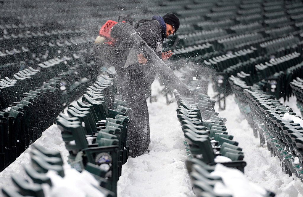 . Johnny Torres is part of a large crew clearing the snow from the seats at Coors Field after a spring snowstorm dumped close to a foot of snow downtown, canceling Monday\'s Rockies game. Weather permitting, the Rockies will play a split double header against the New York Mets  to make up for the missed game on Monday. (Photo By Kathryn Scott Osler/The Denver Post)