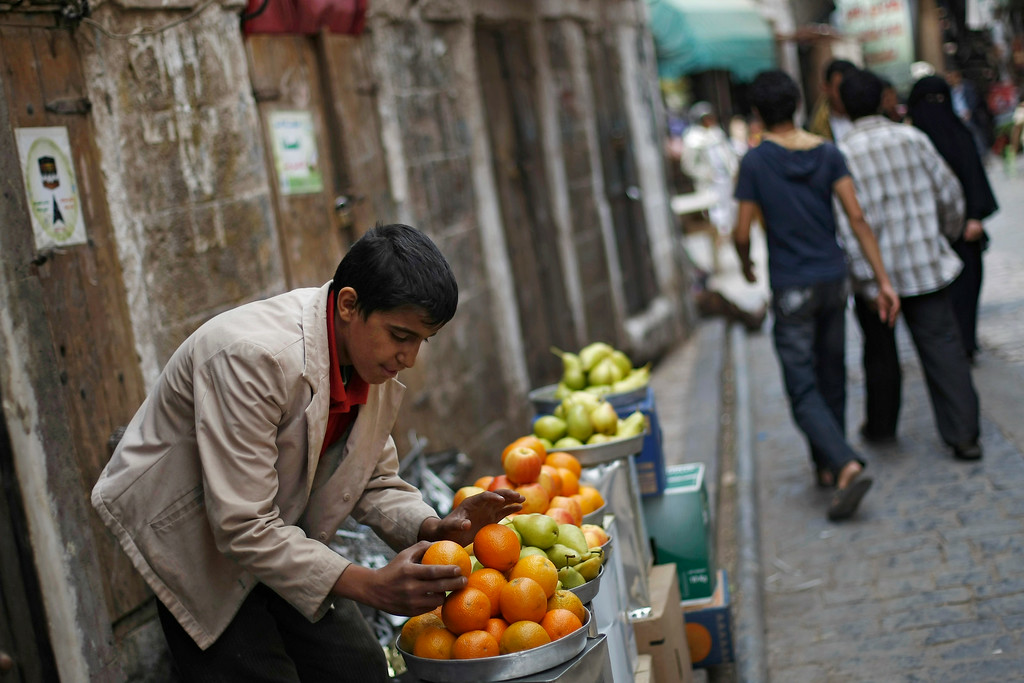 . A Yemeni street vendor displays fruits for sale to be eaten after breaking the fast on the first day of the month of Ramadan in the a market in the old city of Sanaa, Yemen, Saturday, June 28, 2014. (AP Photo/Hani Mohammed)