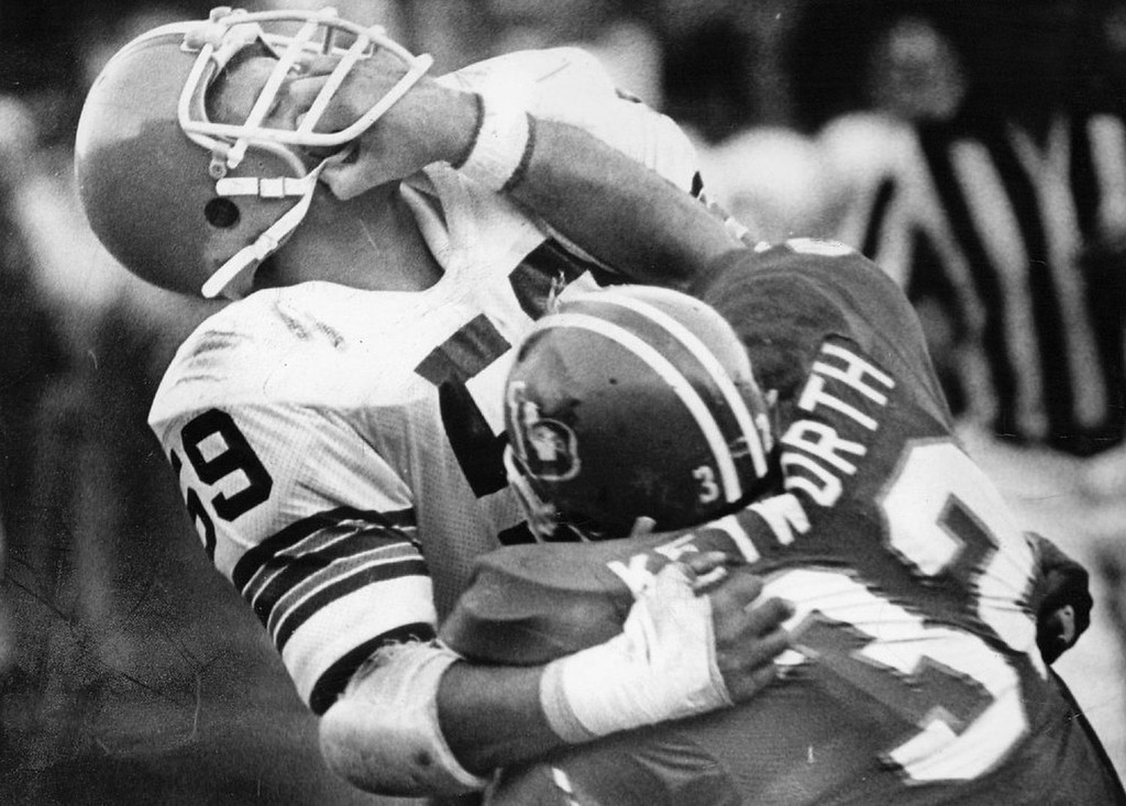 . Bronco running back Jon Keyworth (32) accidentally got a hand stuck in his opponent\'s face mask on this 1975 play. (Photo by John J. Sunderland/Denver Post)