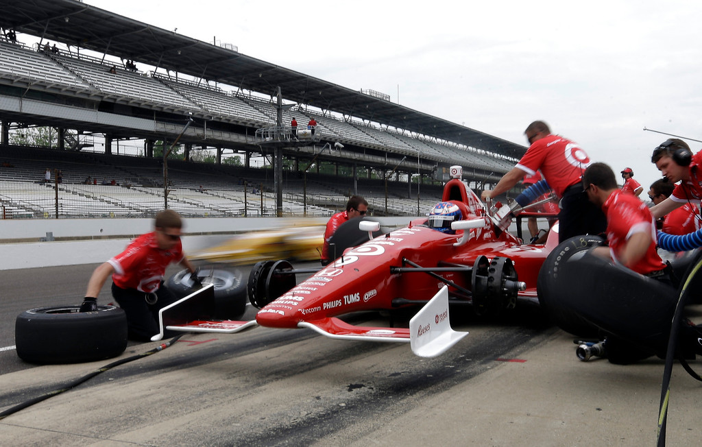 . A car drives by as the crew of Scott Dixon, of New Zealand, practices a pit stop during practice for the Indianapolis 500 auto race at the Indianapolis Motor Speedway in Indianapolis, Thursday, May 16, 2013. (AP Photo/Darron Cummings)