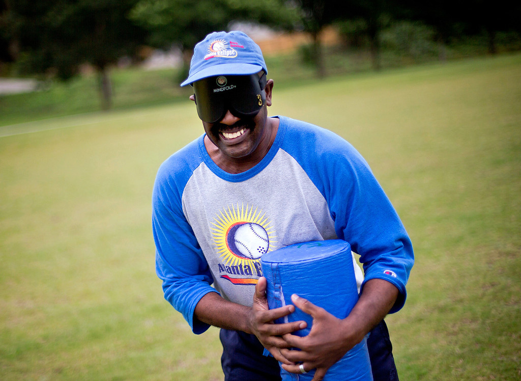 """. Jimmie Burnette, who lost his vision to a brain tumor in 2010, reaches the base after following its buzzing sound during a blind baseball workout in Atlanta. \""""My biggest achievement is I ran, I hit a ball and ran. And I look back at it and say \'wow, I really did that.\' And if I can run to a base, it doesn\'t mean I won\'t give up!\"""" he says. (AP Photo/David Goldman)"""