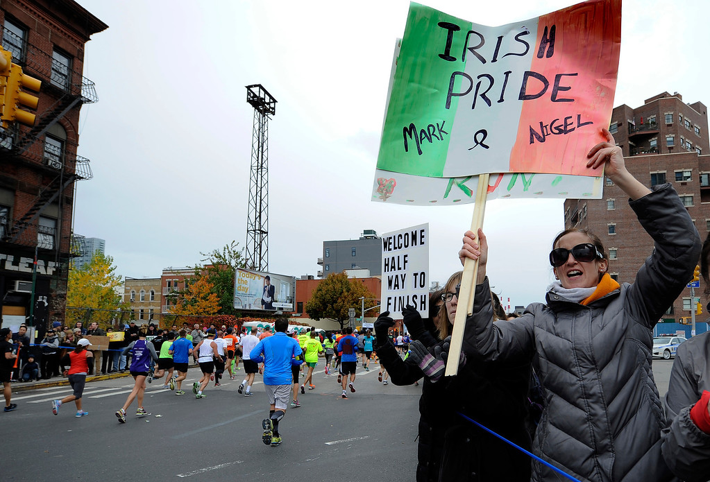 . Fans cheer runners as the enter into the Queens borough of New York from the Pulaski Bridge during the New York City Marathon on Sunday, Nov. 3, 2013. New York. (AP Photo/Kathy Kmonicek)