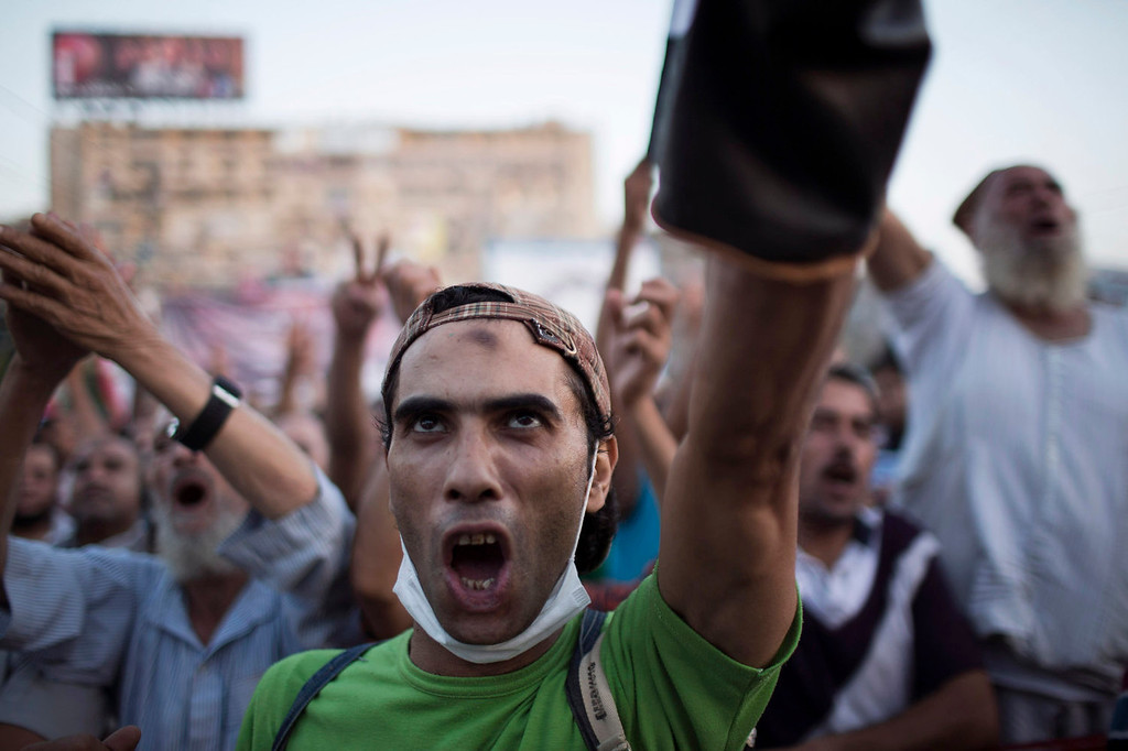 . A supporter of Egypt\'s ousted President Mohammed Morsi chants slogans against Egyptian Army during a protest at the sit-in at Rabaah al-Adawiya mosque, which is fortified with multiple walls of bricks, tires, metal barricades and sandbags, where protesters have installed their camp in Nasr City, Cairo, Egypt, Monday, Aug. 12, 2013. Egyptian authorities on Monday postponed a move to disperse the two Cairo sit-ins by Morsi supporters to \'avoid bloodshed,\' an official said. Islamist supporters demand that Morsi be returned to power. (AP Photo/Manu Brabo)