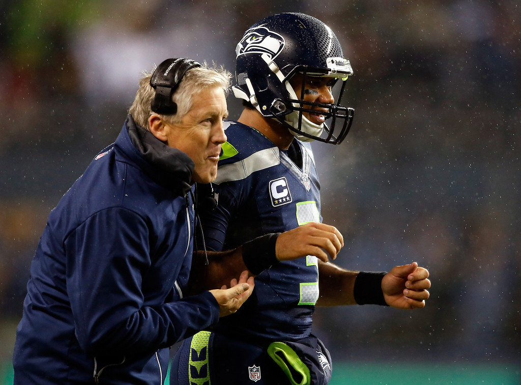 . Quarterback Russell Wilson #3 of the Seattle Seahawks and head coach Pete Carroll celebrate after scoring against the New Orleans Saints during a game at CenturyLink Field on December 2, 2013 in Seattle, Washington.  (Photo by Otto Greule Jr/Getty Images)