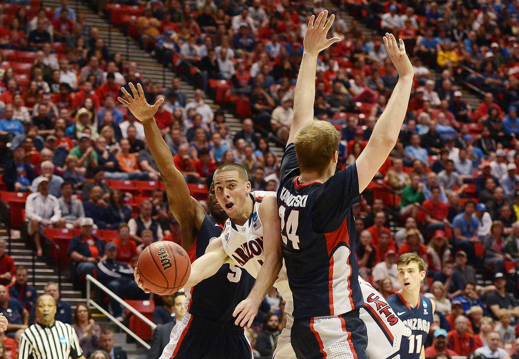 . T.J. McConnell #4 of the Arizona Wildcats passes between Gary Bell, Jr. #5 and Przemek Karnowski #24 of the Gonzaga Bulldogs in the second half during the third round of the 2014 NCAA Men\'s Basketball Tournament at Viejas Arena on March 23, 2014 in San Diego, California.  (Photo by Donald Miralle/Getty Images)