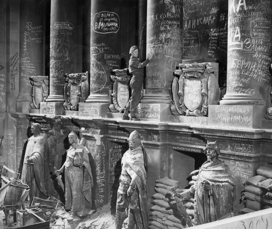 . In the bomb damaged Reichstag, hundreds of Russian soldiers have chalked their names among the stone pillars at the entrance. A newly arrived British Tommy is seen adding his name to the list, May 7, 1945 in Berlin. (AP Photo)
