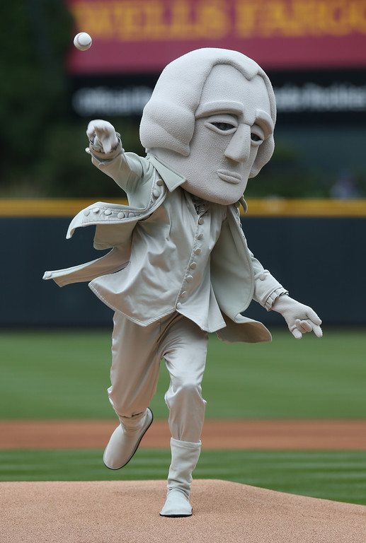 . As part of an effort to promote travel in western South Dakota, a person dressed as George Washington throws out the ceremonial first pitch before the Colorado Rockies host the Los Angeles Dodgers in the first inning of a baseball game in Denver on Saturday, June 7, 2014. (AP Photo/David Zalubowski)