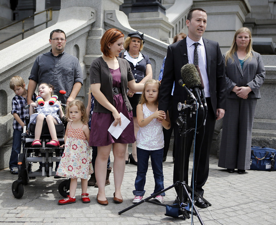 . Family attorney Michael Silverman, right,  holds hands with Coy Mathis as he speaks at a news conference at the Capitol in Denver on Monday, June 24, 2013. Standing next to Coy is her mother Kathryn Mathis. Her father Jeremy Mathis and other siblings are at left. The Colorado Civil Rights Division has ruled in favor of six-year-old Coy Mathis, whose school had barred her from using the girls bathroom at her elementary school because she is transgender.   (AP Photo/Ed Andrieski)
