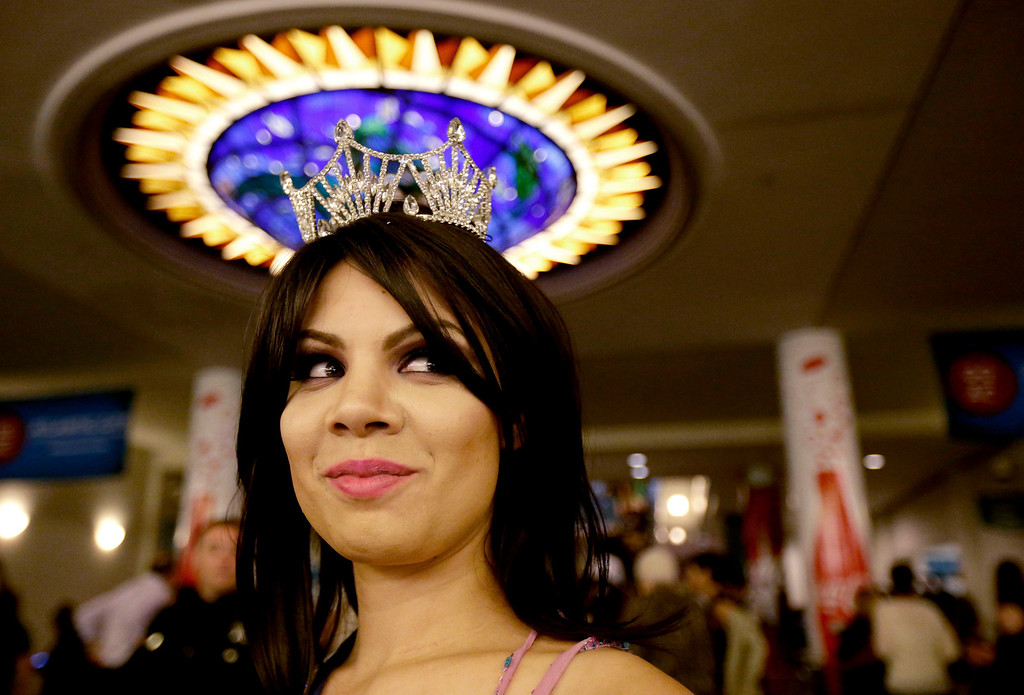 . Miss Puerto Rico Collegiate Shaina Millan waits in the lobby of Boardwalk Hall before the Miss America 2014 pageant, Sunday, Sept. 15, 2013, in Atlantic City, N.J. (AP Photo/Julio Cortez)