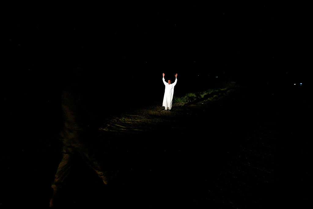 . An Iraqi man raises his hands as he is approached by U.S. soldiers during a night raid June 18, 2005 on the outskirts of Baquba, 70 kilometers (43.5 miles) northeast of Baghdad, Iraq. (Photo by Ghaith Abdul-Ahad/Getty Images).