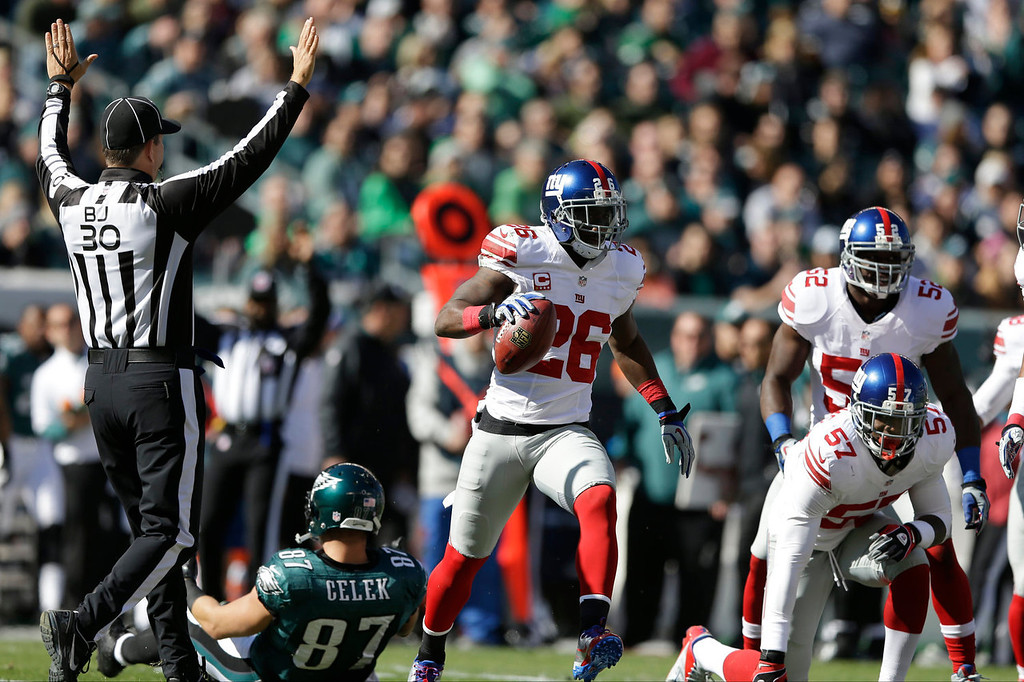 . New York Giants strong safety Antrel Rolle (26) celebrates while running away from Philadelphia Eagles tight end Brent Celek (87) after intercepting a pass during the first half of an NFL football game on Sunday, Oct. 27, 2013, in Philadelphia. (AP Photo/Matt Rourke)