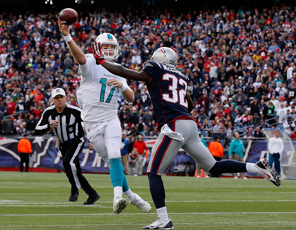 . Ryan Tannehill #17 of the Miami Dolphins throws a touchdown pass by Devin McCourty #32 of the New England Patriots in the first quarter at Gillette Stadium on October 27, 2013 in Foxboro, Massachusetts. (Photo by Jim Rogash/Getty Images)