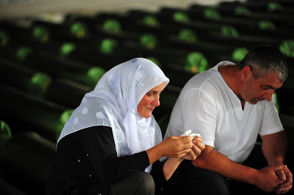 . Bosnian Muslims, survivors of Srebrenica 1995 massacre, pray and cry near body caskets of their relatives, laid out in a factory hangar, near memorial cemetery in village of Potocarion near Eastern-Bosnian town of Srebrenica, on July 10, 2013. Potocari Memorial cemetery is undergoing preparations for another mass burial on July 11, when 409 newly identified bodies will be put to final rest. Bodies are identified as those belonging to Bosnian Muslim victims, of the offensive undertaken by Bosnian Serbs in July 1995 with aim to occupy, earlier declared UN safe heaven area of Srebrenica and the surrounding villages. During the offensive more than 8000 Bosnian non-Serbs went missing to be found buried in mass graves, years after the war ended.  ELVIS BARUKCIC/AFP/Getty Images