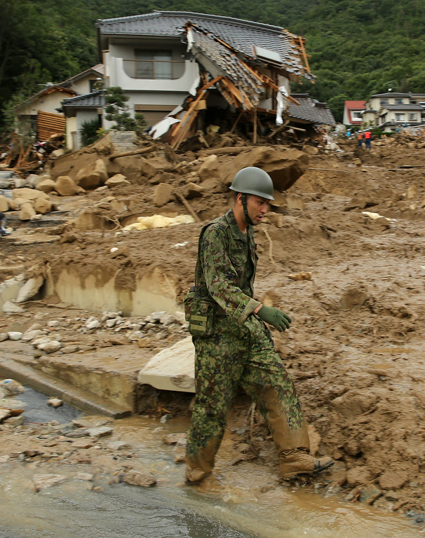 . Members of Ground Self-Defense walks front of the  debris  of houses destroyed by a landslide caused by torrential rain at the site of a landslide in a residential area on August 20, 2014 in Hiroshima, Japan. (Photo by Buddhika Weerasinghe/Getty Images)