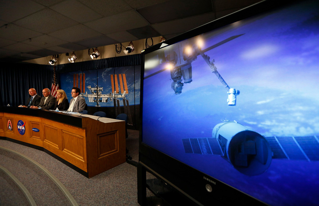 . NASA spokesman Mike Curie, NASA International Space Station Program Manager Mike Suffredini, SpaceX President Gwynne Shotwell and weather officer Joel Tumbiolo (L-R) take part in a pre-launch news conference for the SpaceX Falcon 9 and Dragon capsule at the Kennedy Space Center in Cape Canaveral, Florida February 28, 2013. The rocket is scheduled for launch on a second resupply mission to the International Space Station on March 1. The image on right depicts a previous mission with the Dragon capsule docked at the space station.    REUTERS/Scott Audette