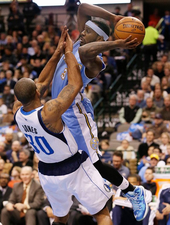 . Ty Lawson #3 of the Denver Nuggets is fouled by Dahntay Jones #30 of the Dallas Mavericks at American Airlines Center on December 28, 2012 in Dallas, Texas.     (Photo by Ronald Martinez/Getty Images)