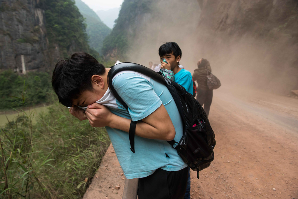 . This photo taken on April 21, 2013 shows people covering their mouths and noses to avoid dust while rocks fall down from mountains on their way home to the city of Ya\'an, southwest China\'s Sichuan province. STR/AFP/Getty Images