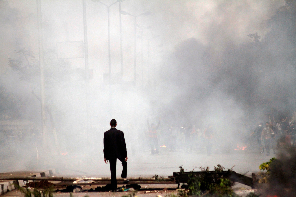 . A man stands amid the smoke from tear gas fired by Egyptian riot police in Cairo, Egypt, Friday, Nov. 29, 2013, to disperse hundreds of Islamist demonstrators defying a new protest law that has drawn widespread criticism from the international community and democracy advocates.(AP Photo/Sabry Khaled, El Shorouk Newspaper)