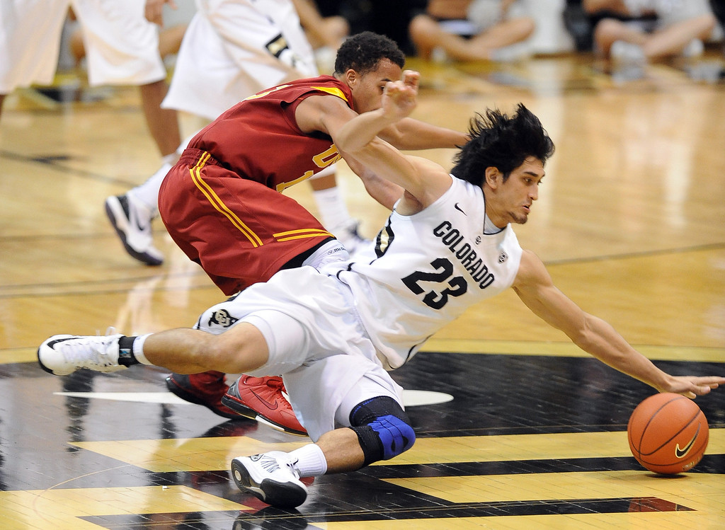 . Sabatino Chen (23) slides in to take the ball away from Chass Bryan of USC during the second half of their Jan. 10, 2013 game in Boulder. (AP Photo/Daily Camera, Cliff Grassmick)