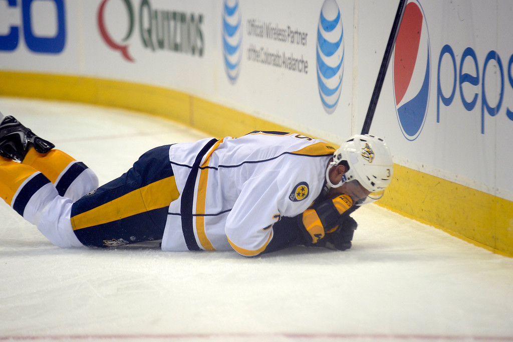 . Nashville Predators defenseman Seth Jones (3) lays on the ice after getting hit into the boards by Colorado Avalanche left wing Jamie McGinn (11) during the first period November 6, 2013 at Pepsi Center. Jones was slow to get up and headed to the locker room. (Photo by John Leyba/The Denver Post)