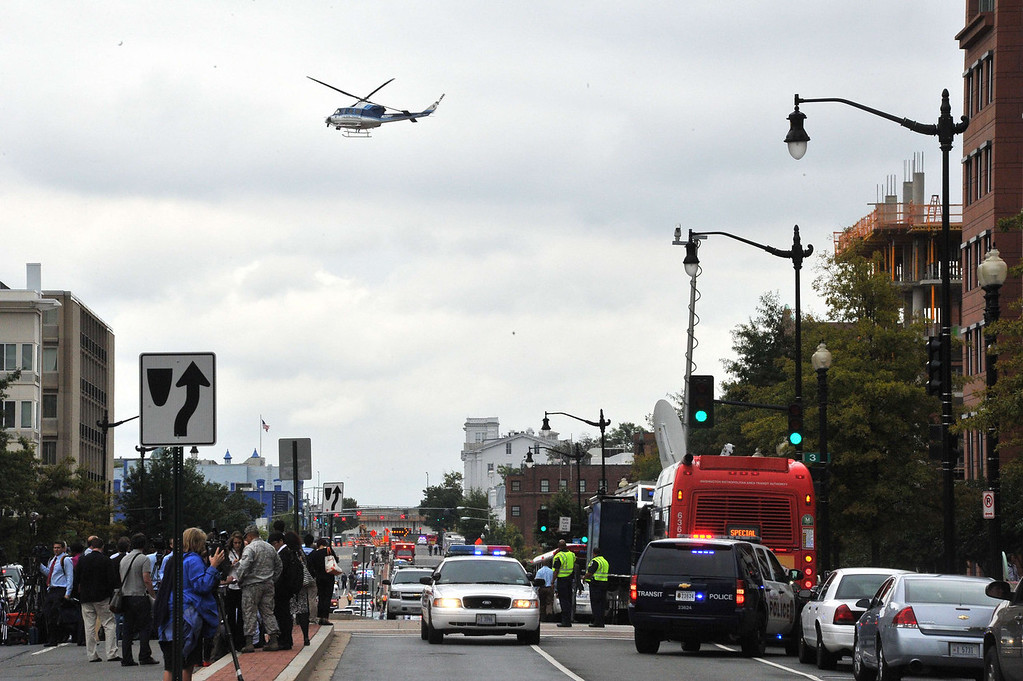 ". Media and emergency response personnel gather outside the US Navy Yard September 16, 2013 in Washington, DC. At least one unidentified gunman opened fire at the US Navy Yard in Washington on Monday and was at large after killing ""multiple\"" victims and wounding several more, officials said. Police and FBI agents descended on the area in force as helicopters swarmed overhead, amid reports a shooter was armed with an assault rifle and was holed up at the complex. \""We believe there were multiple deaths,\"" a US defense official, speaking on condition of anonymity, told AFP. The precise death toll remained unclear, the official said. A Washington DC police officer and another law enforcement officer had been shot while the gunman had allegedly barricaded himself in a room in a headquarters building, media reported.   MLADEN ANTONOV/AFP/Getty Images"