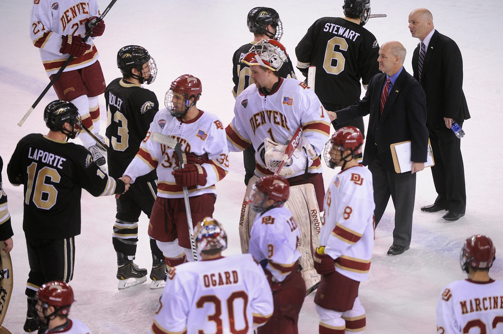 . DENVER, CO. - NOVEMBER 16: Denver coach Jim Montgomery, far right, shook hands with Bronco players after the final period. The University of Denver hockey team defeated Western Michigan 1-0 at Magness Arena Saturday night, November 16, 2013.  Photo By Karl Gehring/The Denver Post