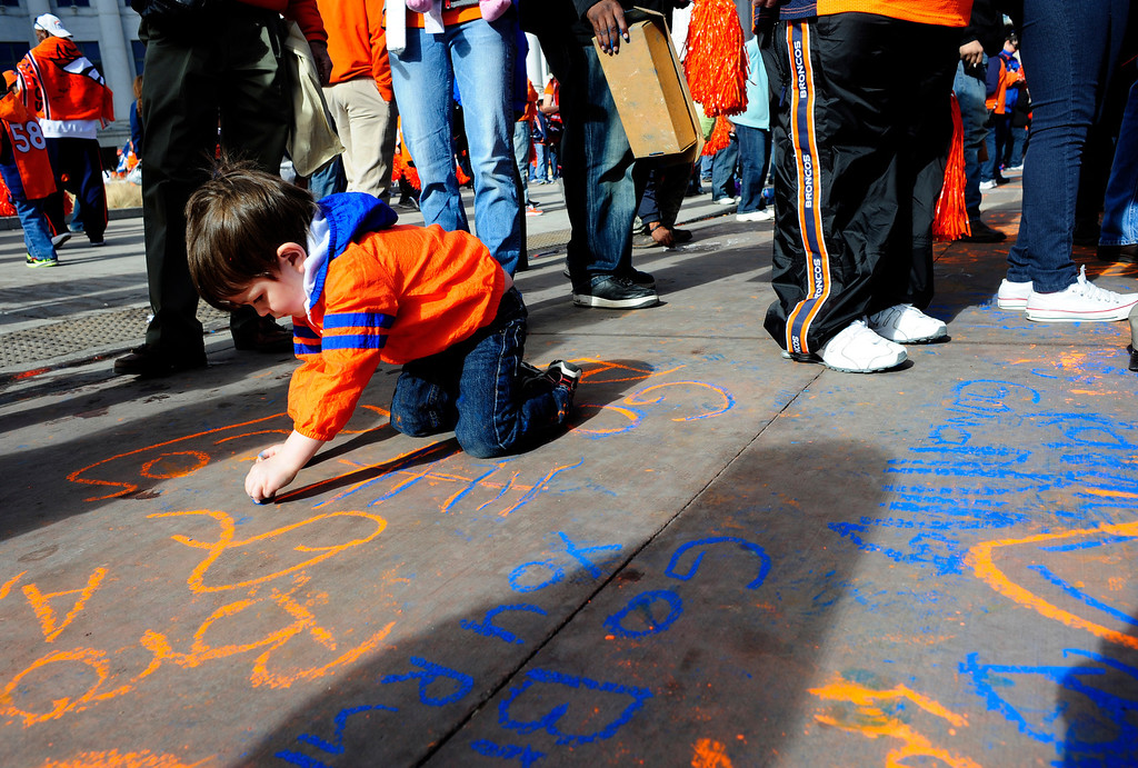 . Christian Clase, 3, draws on Bannock Street using chalk, during a rally to send off the Denver Broncos, at the City and County Building in Denver, Colorado, Sunday, January 26, 2014. The noon rally brought out scores of supporters and included an appearance by Governor John Hickenlooper and Denver Mayor Michael Hancock.  (Photo By Brenden Neville / Special to The Denver Post)