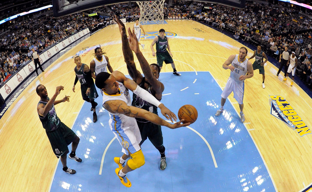 . DENVER, CO. - FEBRUARY 05: Andre Iguodala (9) of the Denver Nuggets passes off past Larry Sanders (8) of the Milwaukee Bucks during the first quarter February 05, 2013 at Pepsi Center. The Denver Nuggets take on the Milwaukee Bucks in NBA action. (Photo By John Leyba/The Denver Post)
